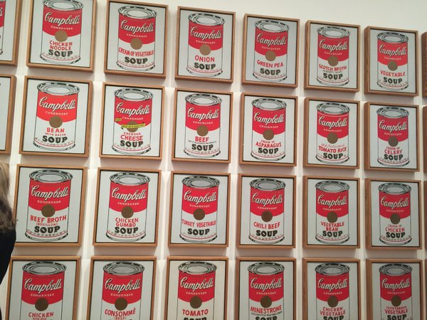 As I enter the floor I see this wall with Campbell's Soup Cans, a work of art produced in 1962 by artist Andy Warhol. Medium : Synthetic Polymer Paint
